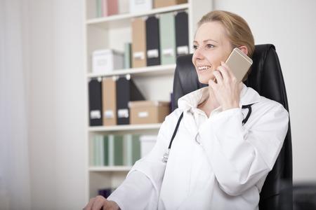 Glimlachende vrouwelijke arts ontspannen bij haar bureau tijdens het bellen naar iemand met een mobiele telefoon Stockfoto - 38964474