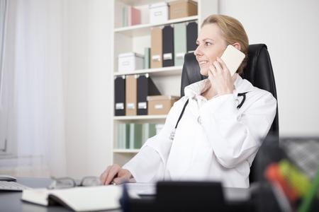 Gelukkig Volwassen Vrouwelijke arts op haar kantoor bellen om iemand op mobiele telefoon tijdens het kijken naar de linkerkant van het frame.