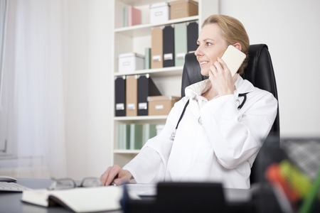 calling on phone: Happy Adult Female Clinician at her Office Calling to Someone on Mobile Phone While Looking to the Left of the Frame. Stock Photo