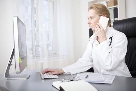 Ernstige volwassen vrouwelijke arts zit aan haar bureau tijdens het bellen om iemand via de telefoon en met behulp van haar Desktop Computer op hetzelfde moment.