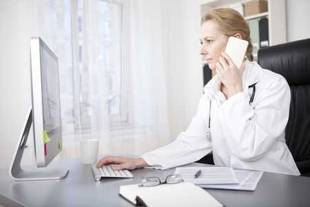 computer device: Serious Adult Female Doctor Sitting at her Desk While Calling to Someone Over the Phone and Using her Desktop Computer at the Same Time.
