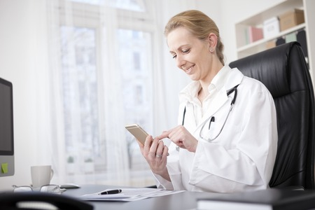 smartphones: Happy Female Medical Doctor Sitting at her Table and Browsing Something on her Mobile Phone
