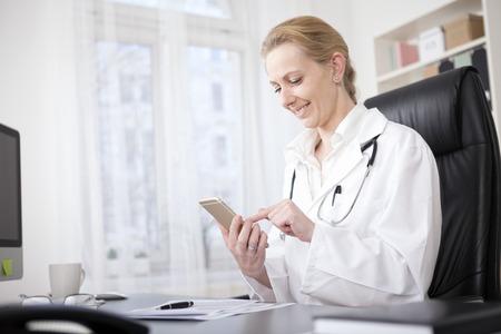 lekarz: Szczęśliwa Kobieta Lekarz Siedząc przy stole i Przeglądając Coś na jej telefon komórkowy