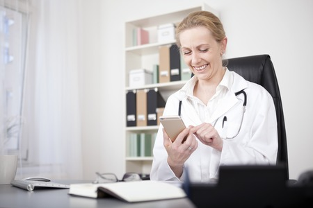 Happy Adult Woman Physician Busy Chatting to Someone Using her Mobile Phone While Sitting at her Office. Standard-Bild