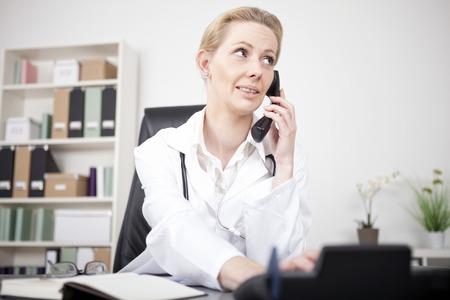 Close-up Ernstige volwassen vrouwelijke arts belt iemand via telefoon tijdens de vergadering op haar bureau en op zoek naar rechtsboven. Stockfoto