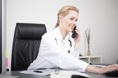 Close up Happy Adult Female Doctor in Medical Suit at her Office Calling Someone Through Telephone photo
