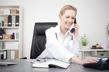 Happy Adult Woman Physician in White Medical Gown Leaning on her Table While Talking to Someone Over the Phone