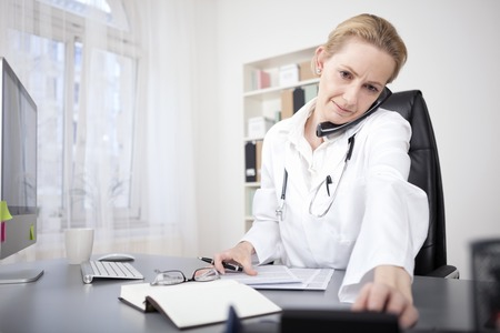 Serious Female Doctor at her Office Holding a Phone Between Ear and Shoulder While Dialing a Phone Number. photo