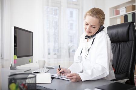 Ernstige Vrouwelijke Arts Grijpen Telefoon Tussen oor en schouder tijdens het schrijven op haar bureau. Stockfoto