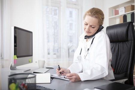 Serious Female Doctor Gripping Telephone Between Ear and Shoulder While Writing at her Desk.
