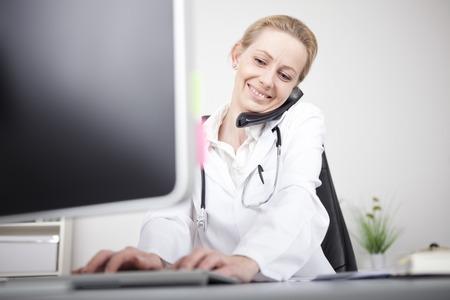 Close-up Gelukkige Vrouw arts bellen op de telefoon tijdens het gebruik van haar computer op de tabel