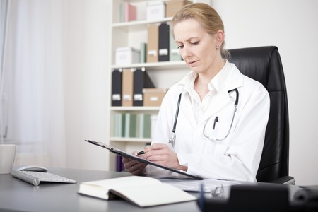 serious doctor: Serious Adult Woman Doctor at her Office Reviewing her Written Medical Findings on the Paper Attached to a Clipping Board.