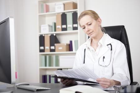 Volwassen vrouw arts Lezing van medische rapporten op een Clipping raad Serieus tijdens de vergadering op haar bureau. Stockfoto