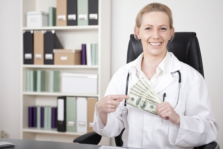 doctor with money: Close up Happy Adult Woman Doctor Holding US Dollars Like a Fan and Pointing to it While Sitting at her Office and Looking at the Camera.