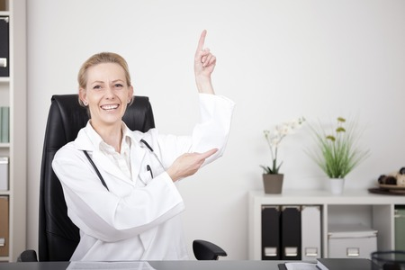 Happy Adult Female Doctor Sitting at her Office and Point to Upper Right with Copy Space While Looking at the Camera photo
