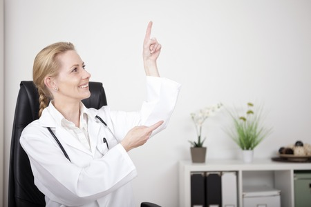 Smiling Woman Physician Pointing and Looking to Upper Right Side with Copy Space While Sitting at her Office. photo