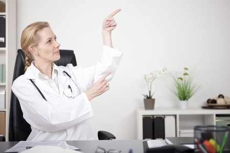 emphasizing: Sitting Female Doctor at her Office Pointing to Upper Right Side with Text Space, Emphasizing Advertisement. Stock Photo