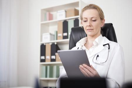 Ernstige vrouwelijke arts te kijken naar het scherm van haar Tablet Hold door haar hand tijdens de vergadering op haar bureau. Stockfoto