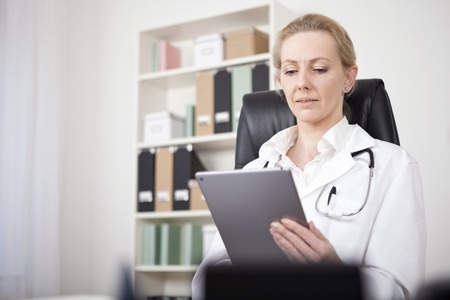 Serious Female Doctor Looking at the Screen of her Tablet Hold by her Hand While Sitting at her Office.