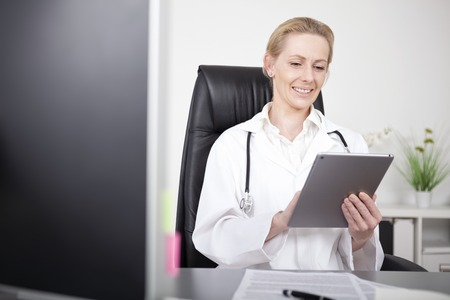 Happy Adult Female Clinician Browsing Internet Using her Tablet Computer While Sitting at her Office. Standard-Bild