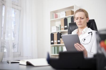 Ernstige volwassen vrouwelijke arts Lezing bij haar tablet-computer tijdens de vergadering op haar bureau.