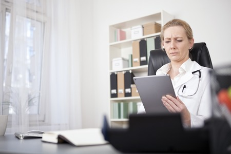 smiling doctor woman: Serious Adult Female Medical Doctor Reading at her Tablet Computer While Sitting at her Desk. Stock Photo