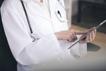 Close-up arts in wit pak met een stethoscoop Bezige Surfen op haar tablet-computer.