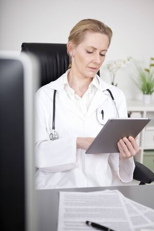 serious doctor: Serious Adult Woman Doctor Browsing at her Tablet Computer While Sitting at her Worktable