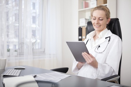 Happy Adult Woman Physician Busy Browsing at her Tablet Device While Sitting Inside her Office. Standard-Bild
