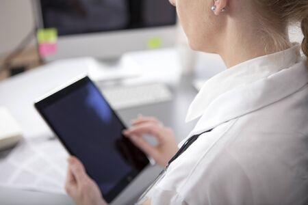 Close-up Moderne Vrouw arts met een tablet-computer met een leeg scherm Terwijl bij het Bureau.