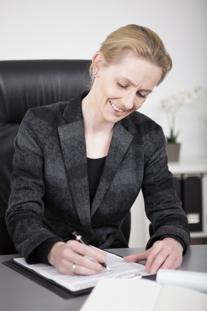Close up Sitting Happy Businesswoman in Black Office Attire Writing on a Paper at her Desk. photo