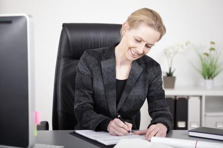 Gelukkig Office Woman in Black Zakelijk Suit Het schrijven van een document tijdens de vergadering op haar tafel. Stockfoto