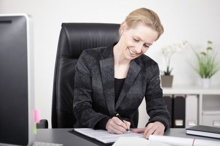 Happy Office Woman in Black Corporate Suit Writing a Document While Sitting at her Table.