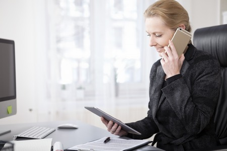 calling on phone: Close up Happy Businessman in Black Suit Looking at her Tablet Screen While Talking to Someone on Mobile Phone Stock Photo