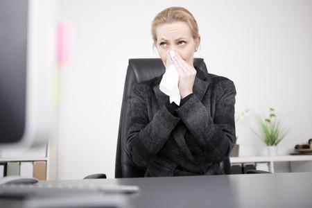 estornudo: Rubia seria Empresaria en traje Negro sopla su nariz mientras estaba sentado en su oficina y que mira lejos. Foto de archivo