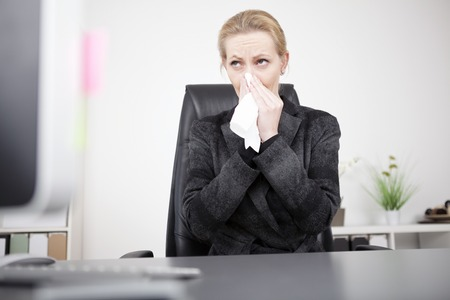 sneeze: Serious Blond Businesswoman in Black Suit Blowing her Nose While Sitting at her Office and Looking Afar.