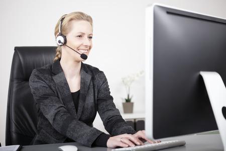 Glimlachende Vrouwelijke Customer Service Representative typen op de computer tijdens de vergadering op haar bureau.