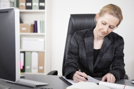 Close up Sitting Businesswoman in Black Business Suit Writing Documents on Top of her Desk Seriously. photo