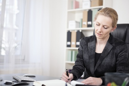 Close up Adult Businesswoman in Black Suit, Sitting at her Desk, Writing on Paper Seriously. photo