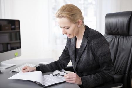Close-up Ernstige Blonde zakenvrouw op haar kantoor scannen zakelijke documenten met een vergrootglas.