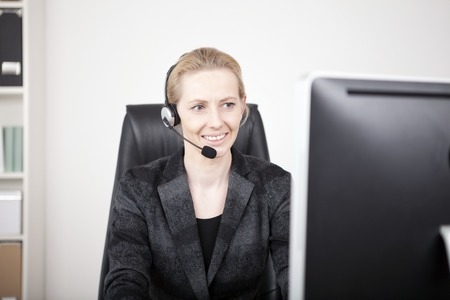 sales call: Smiling Female Customer Support in Black Business Attire Sitting at her Office While Facing her Computer Screen.