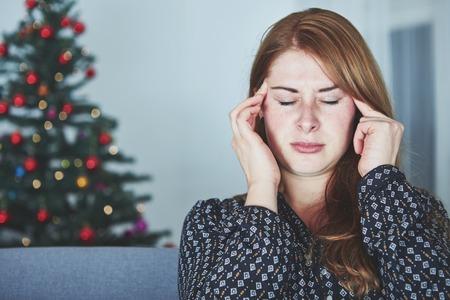 Jonge ongelukkige meisje heeft hoofdpijn van spanning met kerst boom op achtergrond Stockfoto - 48068903
