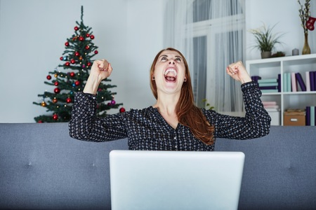 girl with laptop: at christmas young girl raise arms into the air and screams at laptop and is very happy