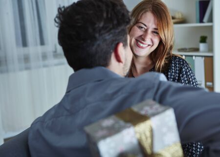gift behind back: young man surprise girlfriend with gift for christmas with present box behind his back Stock Photo