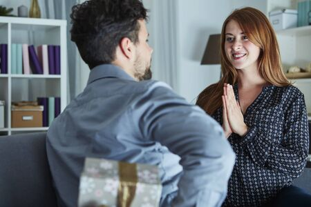 christmas present box: young man surprise girlfriend with gift for christmas with present box behind his back Stock Photo
