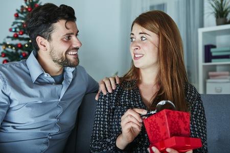 mujer decepcionada: novia mira escéptico a su regalo de Navidad con lupa