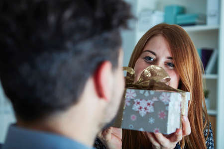 xmas tree: young happy girl suprise her boyfriend with christmas gift Stock Photo
