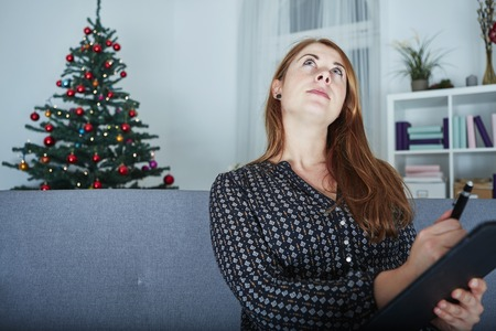 to think about: young happy woman think about christmas wih list on sofa in front of christmas tree.
