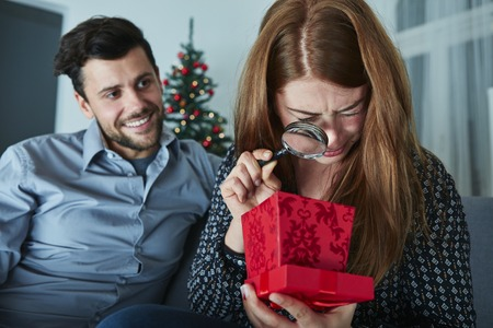 PRESENT: girlfriend looks sceptical to her christmas gift with magnifier Stock Photo