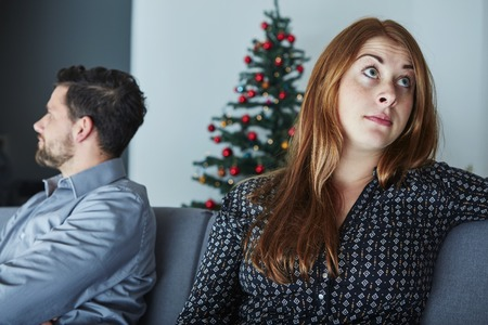 young modern couple is irritated of christmas with christmas tree in background 版權商用圖片 - 48072294